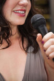 Close up of beautiful woman singing into a microphone — Stock Photo