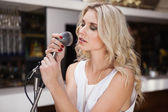 Woman singing while closing her eyes — Stock Photo