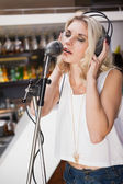 Pretty blonde with headphone singing into microphone — Stock Photo