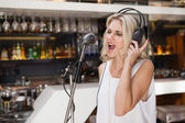 Woman with headphone singing while closing her eyes — Stock Photo