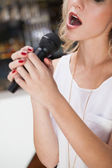 Close up of beautiful blonde singing into a microphone — Stock Photo