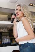 Pretty blonde woman holding a micro while singing — Stockfoto