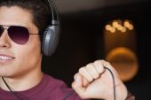Man in sunglasses listening to music with headphone — Stock Photo