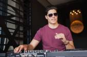 Cool dj in sunglasses working on a sound mixing desk — Stock Photo