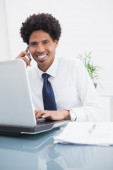Happy businessman phoning and using laptop — Stock Photo