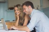 Cute couple using laptop together — Stock Photo