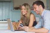 Cute couple using laptop together to shop online — Stock fotografie