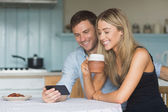 Cute couple using smartphone together — Stock Photo