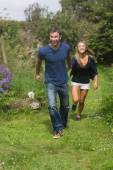 Cute couple running holding hands — Stock Photo