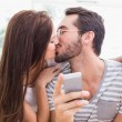 Young man using smartphone while girlfriend kisses him — Stock Photo #60825661