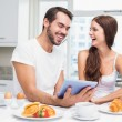Young couple using tablet at breakfast — Stock Photo #60825825