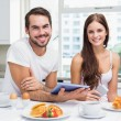 Young couple using tablet at breakfast — Stock Photo #60825841