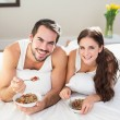 Young couple having breakfast in bed — Stock Photo #60826319