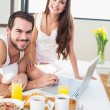 Young couple having breakfast in bed — Stock Photo #60826355