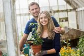 Cute couple gardening in greenhouse — Stock Photo