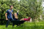 Man pushing his girlfriend in a wheelbarrow — Photo