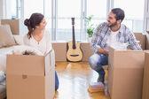 Cute couple unpacking cardboard boxes — Stock Photo