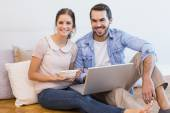 Cute couple sitting on floor using laptop — Stock fotografie
