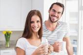 Young couple smiling at the camera having coffee — Stock Photo