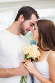 Young man giving girlfriend white roses — Stockfoto