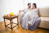 Cute couple relaxing on couch under blanket — Stock Photo