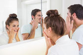 Young couple putting on face cream — Stockfoto