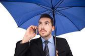 Serious businessman under umbrella phoning — Stock Photo