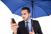 Concentrated businessman under umbrella using mobile — Stock Photo