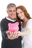 Casual couple showing their piggy bank — Stockfoto