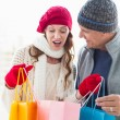 Happy couple in warm clothing opening shopping bags — Stock Photo #60831311