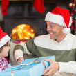 Son giving father a christmas gift on the couch — Stock Photo #60833479