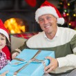 Son giving father a christmas gift on the couch — Stock Photo #60833487