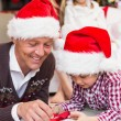 Festive father and son opening christmas present — Stock Photo #60836137