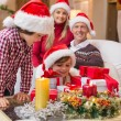 Smiling family at christmas time with lots of presents — Stock Photo #60836417