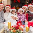 Happy extended family looking at camera at christmas time — Stock Photo #60836443