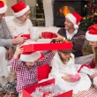 Happy family opening christmas gifts together — Stock fotografie #60837027