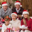 Portrait of a happy extended family in santa hat holding gifts — Stock Photo #60837099