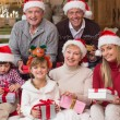 Portrait of a happy extended family in santa hat holding gifts — Stock Photo #60837105