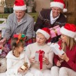 Happy family exchanging christmas gifts — Stock Photo #60837111