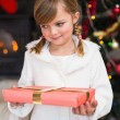 Portrait of a smiling little girl holding a wrapped gift — Stock Photo #60837275