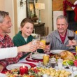 Multi generation family toasting each other at dinner — Stock Photo #60837583