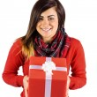 Smiling brunette showing a gift with white bow — Stock Photo #60839891