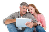 Casual couple sitting using tablet — Stock Photo