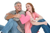 Casual couple holding pink heart — Stock Photo