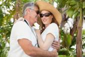 Holidaying couple hugging and smiling  — Stock Photo