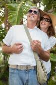 Holidaying couple smiling and looking up — Stock Photo