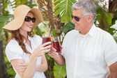 Holidaying couple toasting with cocktails — Stock Photo