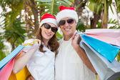Festive couple holding shopping bags — Stock Photo