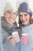 Happy couple in warm clothing holding mugs — Stock Photo