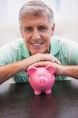 Smiling mature man with piggy bank — Stock Photo